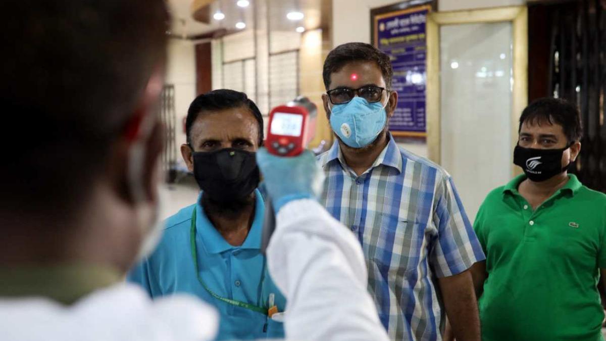 Gent amb mascaretes i a qui se'ls pren la temperatura a Bangladesh