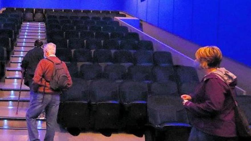 Tres espectadores entran en una sala de cine.