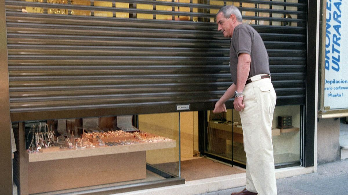 Un hombre cierra la persiana de su negocio