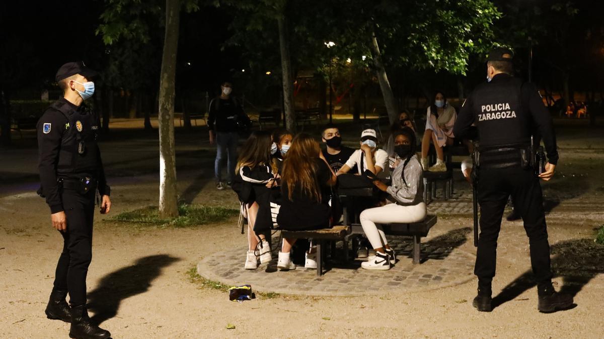 Levantado el toque de queda, unos jóvenes en el parque de La Granja de Zaragoza ante la mirada de la Policía