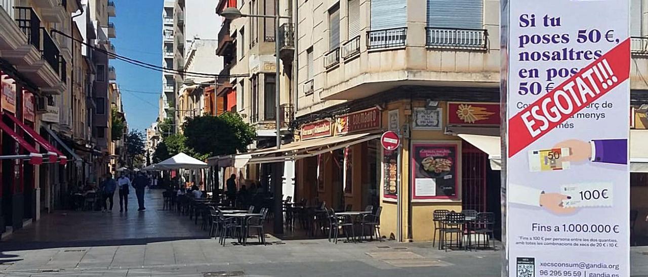 La plaza del Prado y la calle Rausell, ayer, con un tótem que anuncia el fin de cheque consumo».      | LEVANTE-EMV