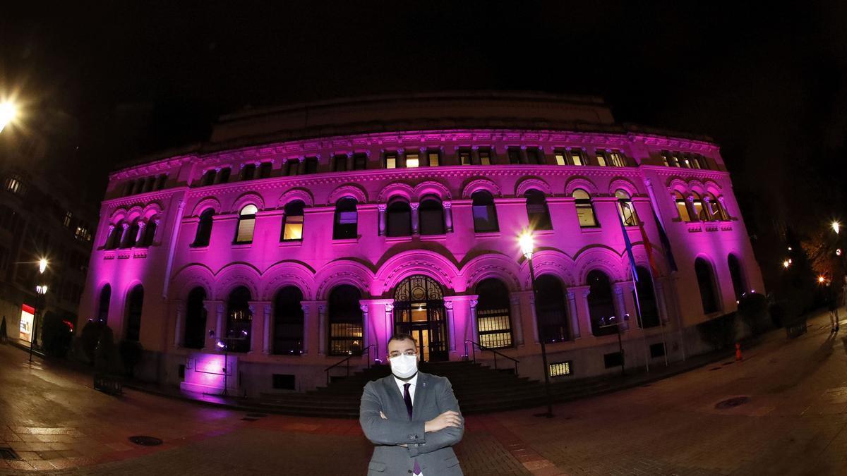 Adrián Barbón, posando delante de la sede de Presidencia, iluminada de morado.
