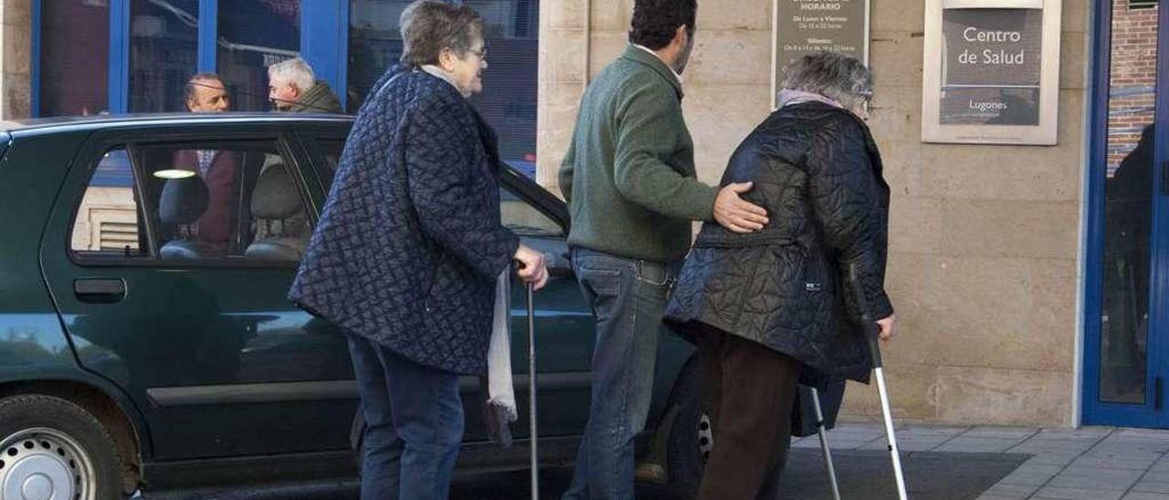 Dos personas con movilidad reducida se dirigen a la entrada del centro de salud.