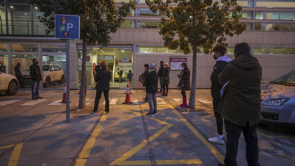 Pacientes esperando ayer por la tarde a la entrada del centro de salud de El Toscar en Elche.