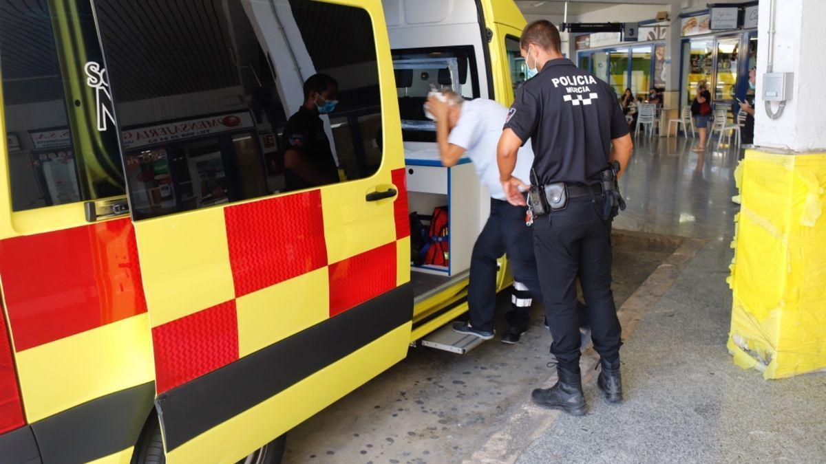 El herido entra en la ambulancia, en presencia de un agente.