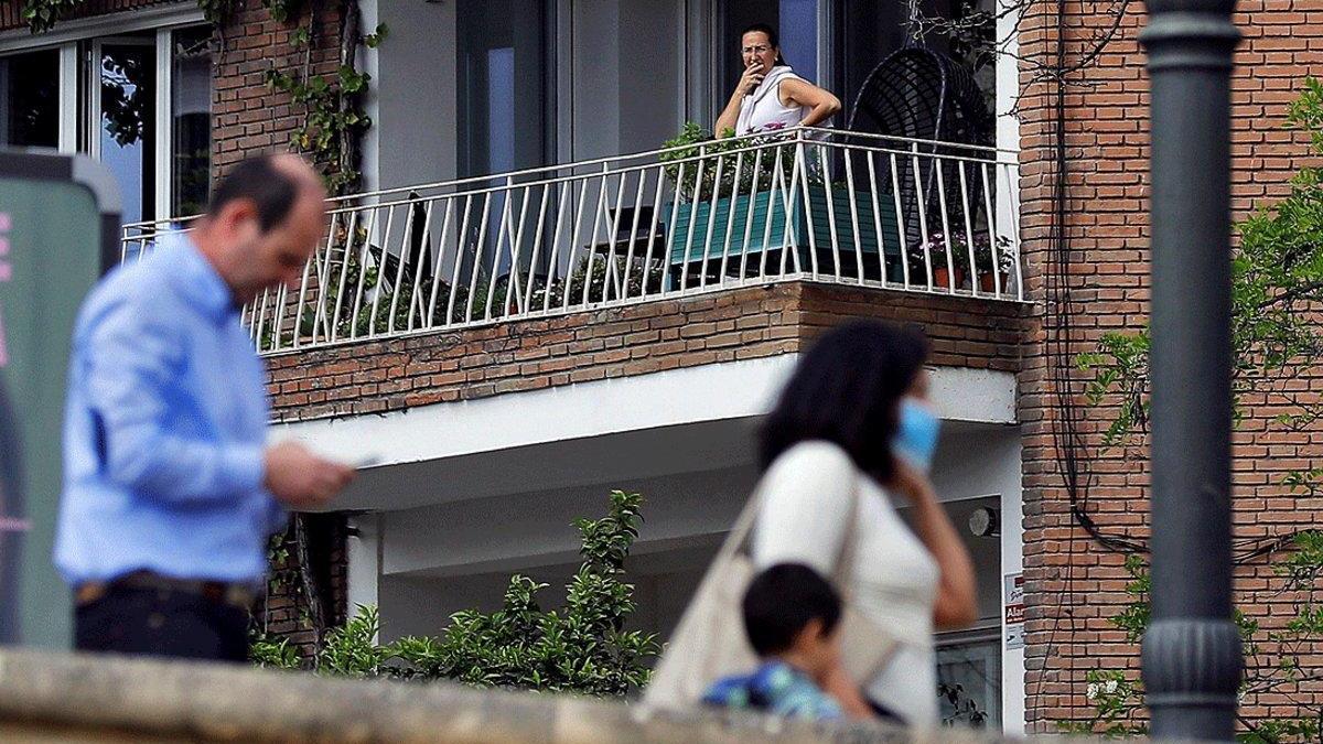 Una mujer observa desde su balcón a una familia paseando.