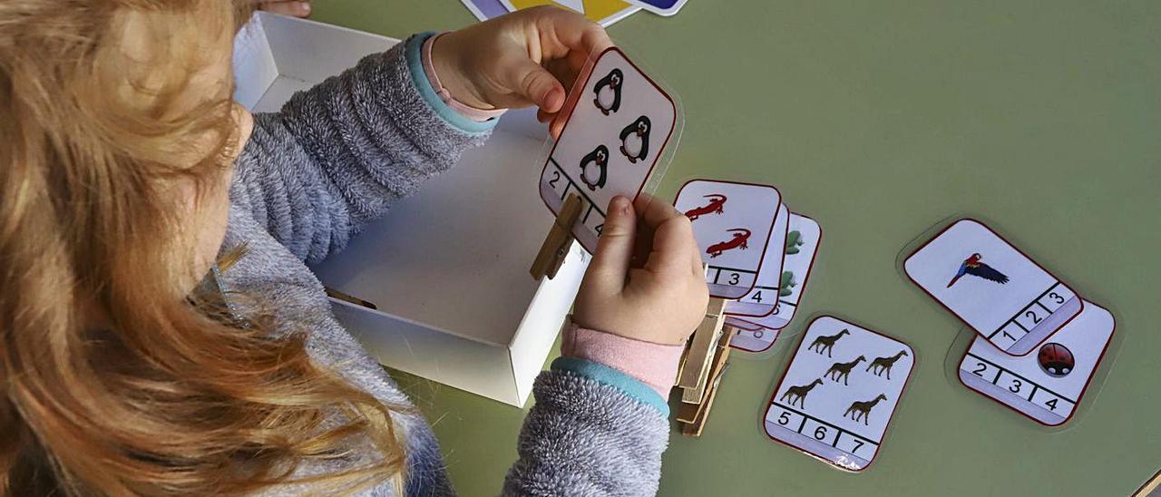 Una niña aprende con cartas en un colegio.  d.tortajada