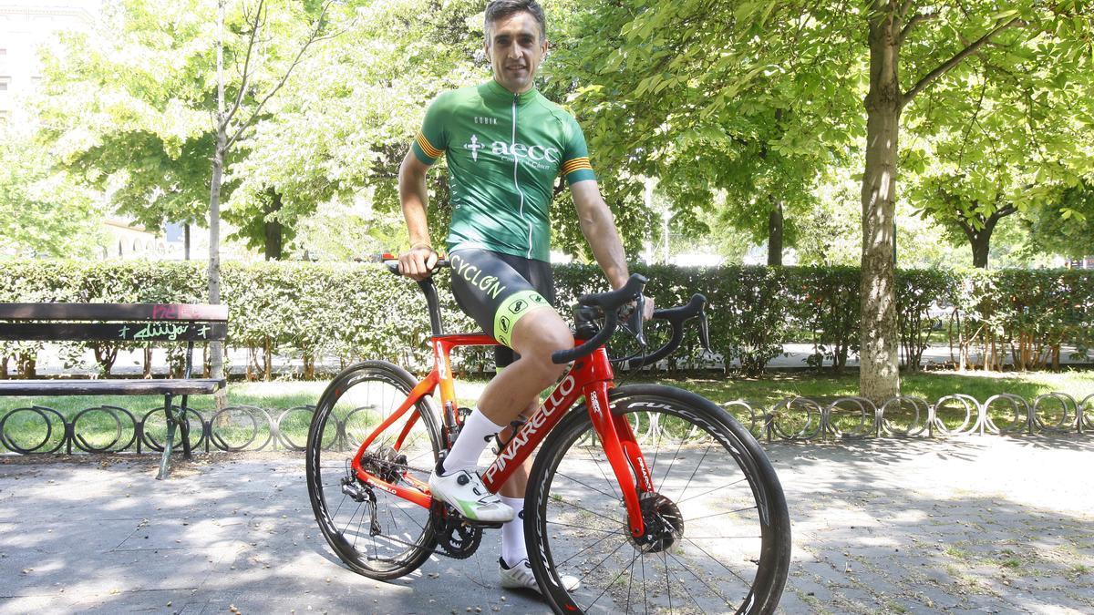 Un voluntario de la AECC posa con el maillot de la carrera y su bicicleta.