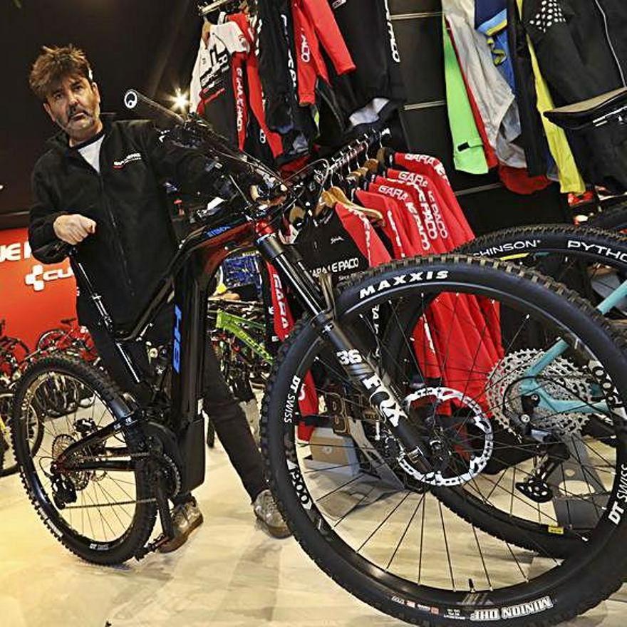 Armando Cuendias amuesa una bicicleta eléctrica de monte na so tienda d'Avilés.   Ricardo Solís