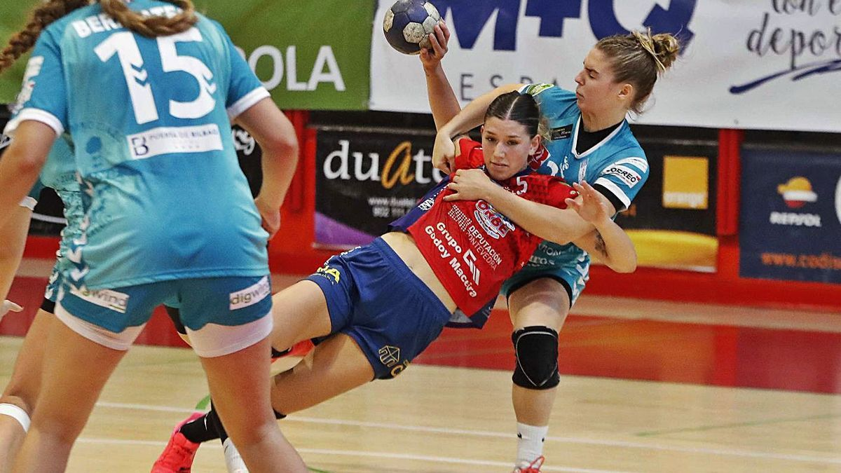 Una jugadora del BM Zuazo agarra a una rival del BM Porriño en posición de tiro. |  // PABLO HERNÁNDEZ