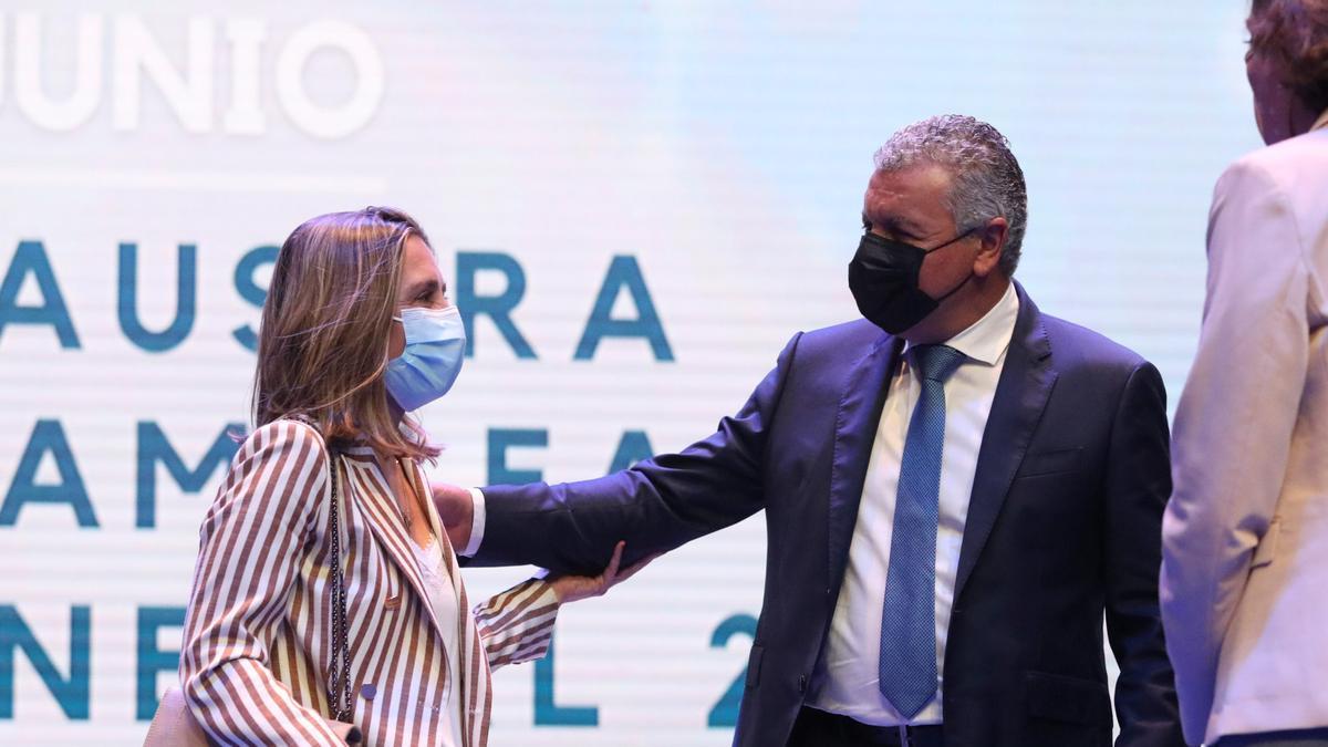 María Calvo recibe el saludo de Belarmino Feito; de espaldas, la Ministra Reyes Maroto.