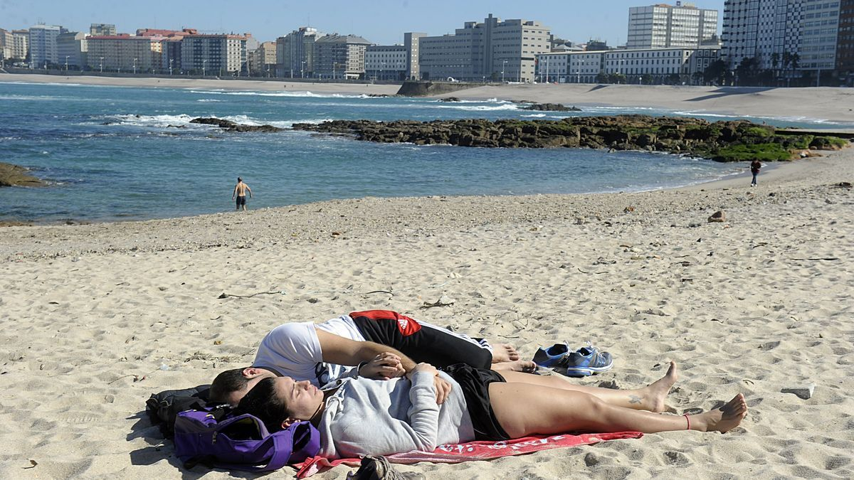 Dos personas al sol en la playa de Riazor. / Víctor Echave