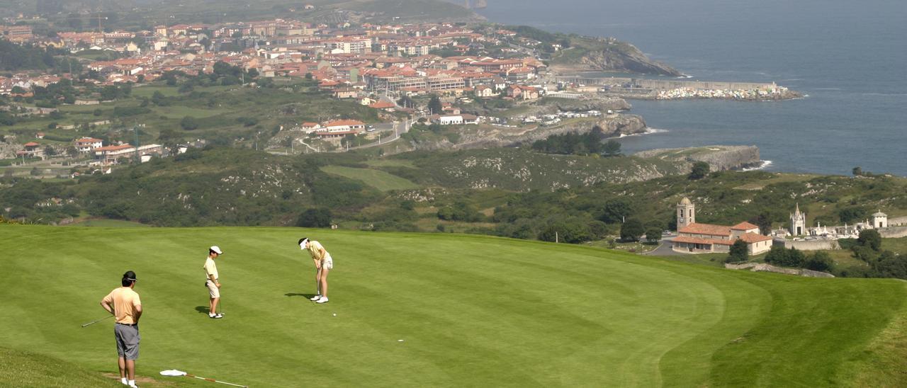 Jugadores practicando golf; al fondo, la villa de Llanes.