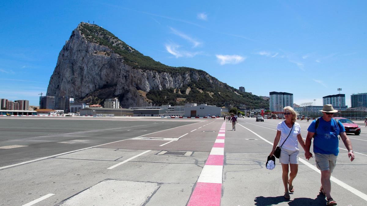 Dos turistas, en la pista del aeropuerto de Gibraltar.