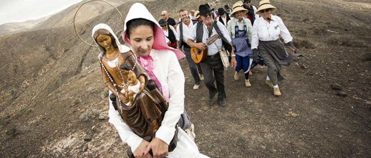 Los romeros cargan la imagen de la Virgen del Tanquito durante el trayecto hacia la cima de la montaña de El Cardón, ayer.