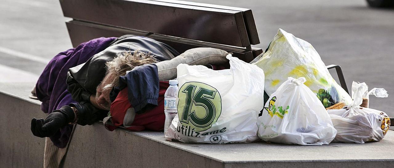 Persona sin hogar durmiendo en un banco.