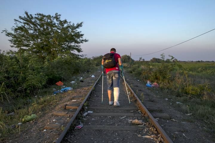 A migrant, hoping to cross into Hungary, walks along a railway track near the village of Horgos in Serbia, towards the border it shares with Hungary