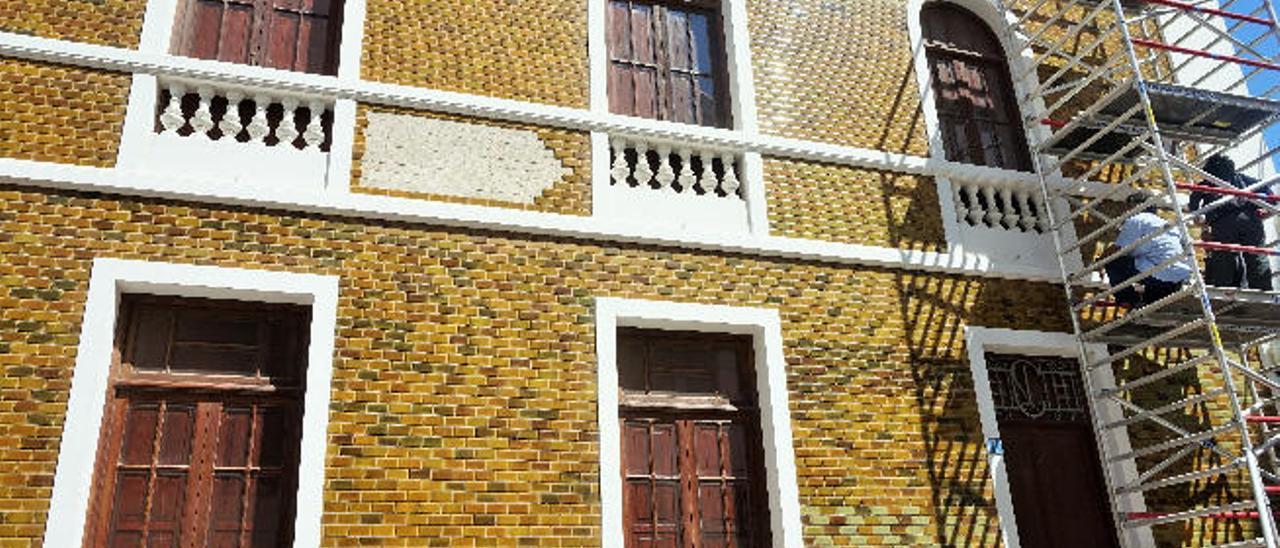 Los técnicos, en el andamio colocado ayer. Entre las dos ventanas superiores, una de las zonas sin azulejos.