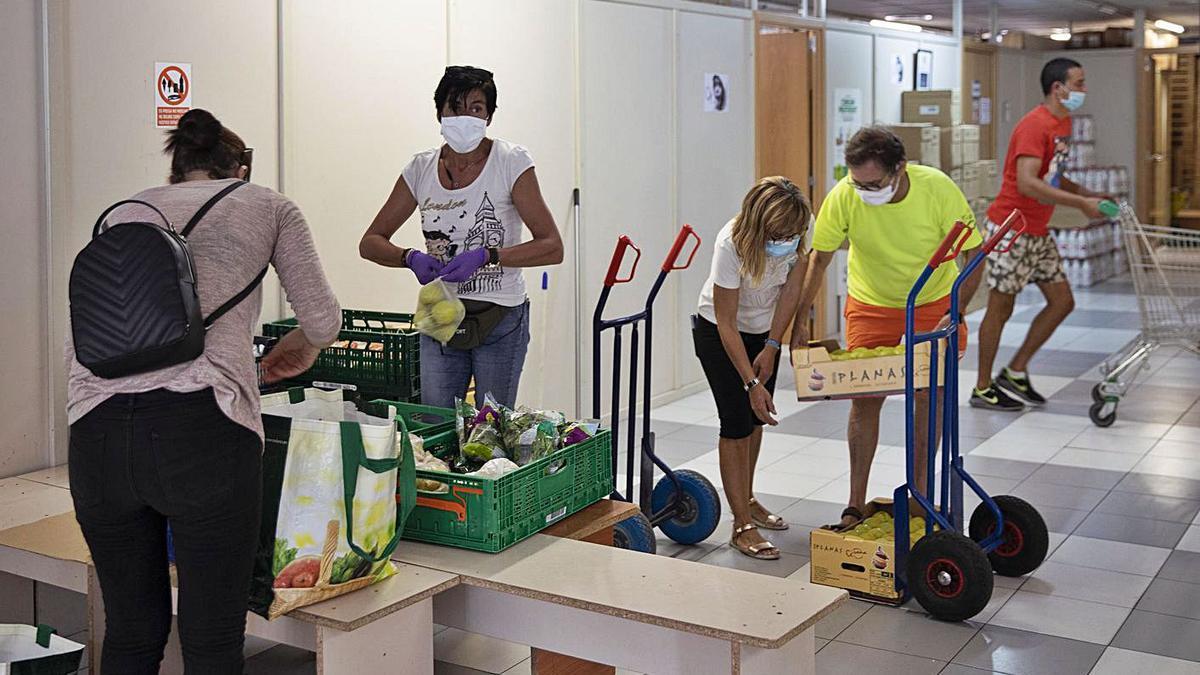 Voluntaris de Càritas a Blanes preparant lots d'aliments, durant la pandèmia.    DAVID APARICIO