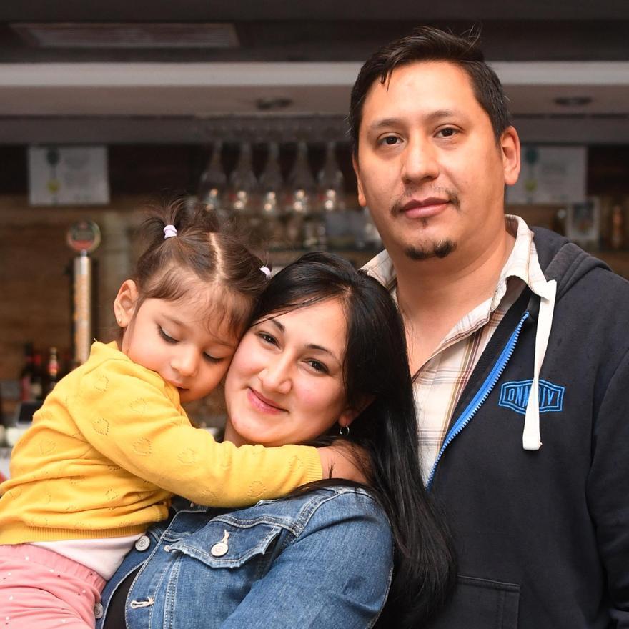 Nadia Pereyra y Fabián López Casco, con su hija, Antonella, en su pizzería del barrio coruñés de Os Mallos.