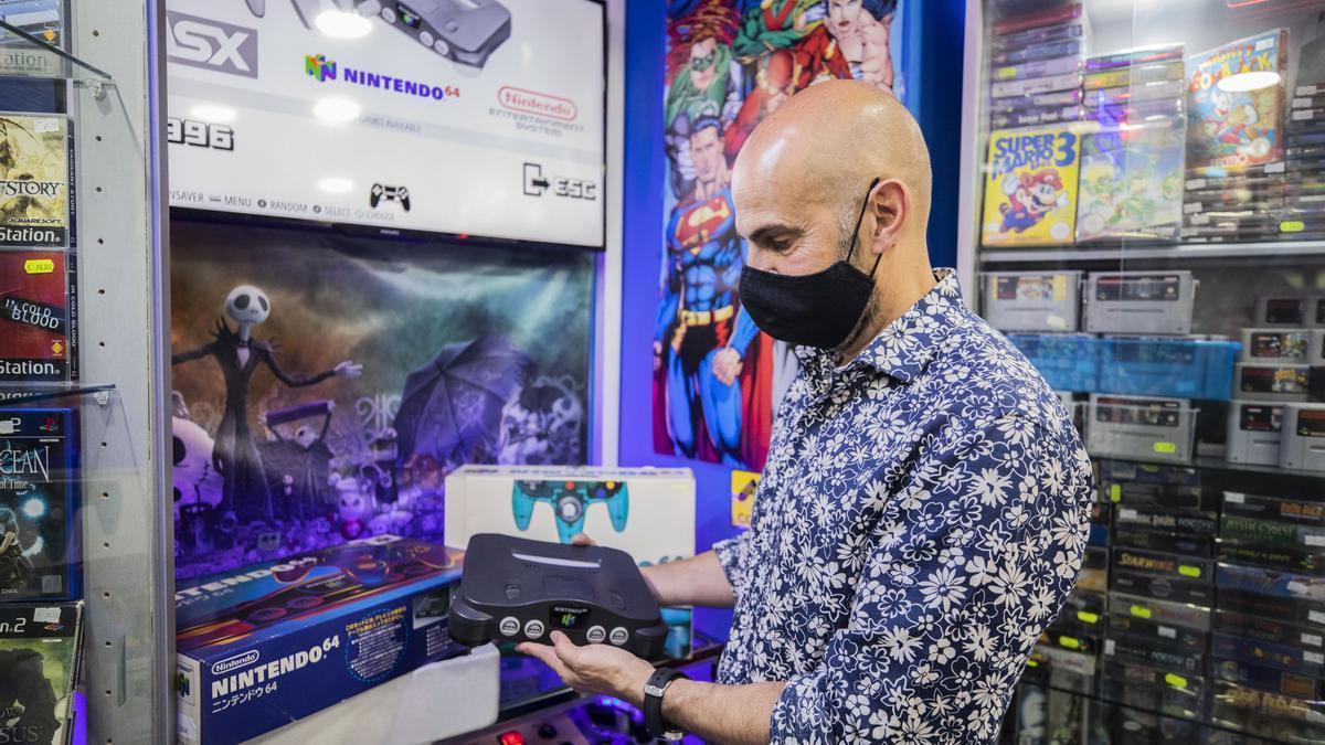 Jiménez, con una consola antigua de las que vende en su tienda de videojuegos Star Games.