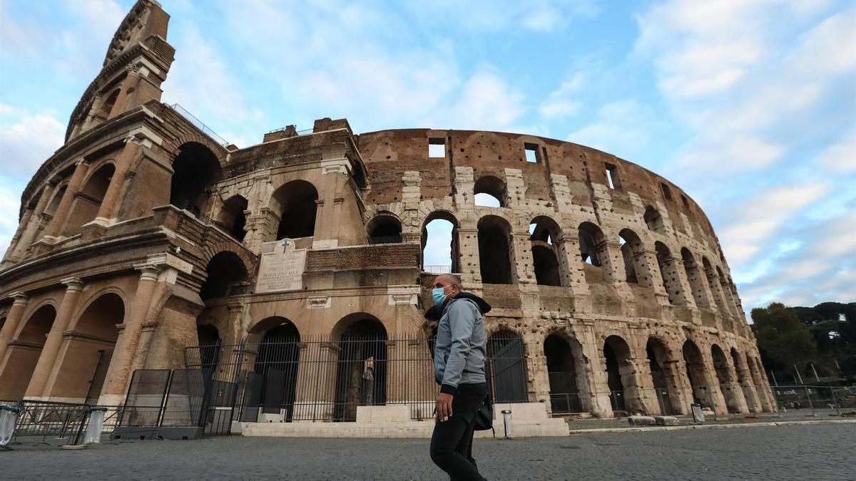 Un hombre camina frente al Coliseo de Roma.