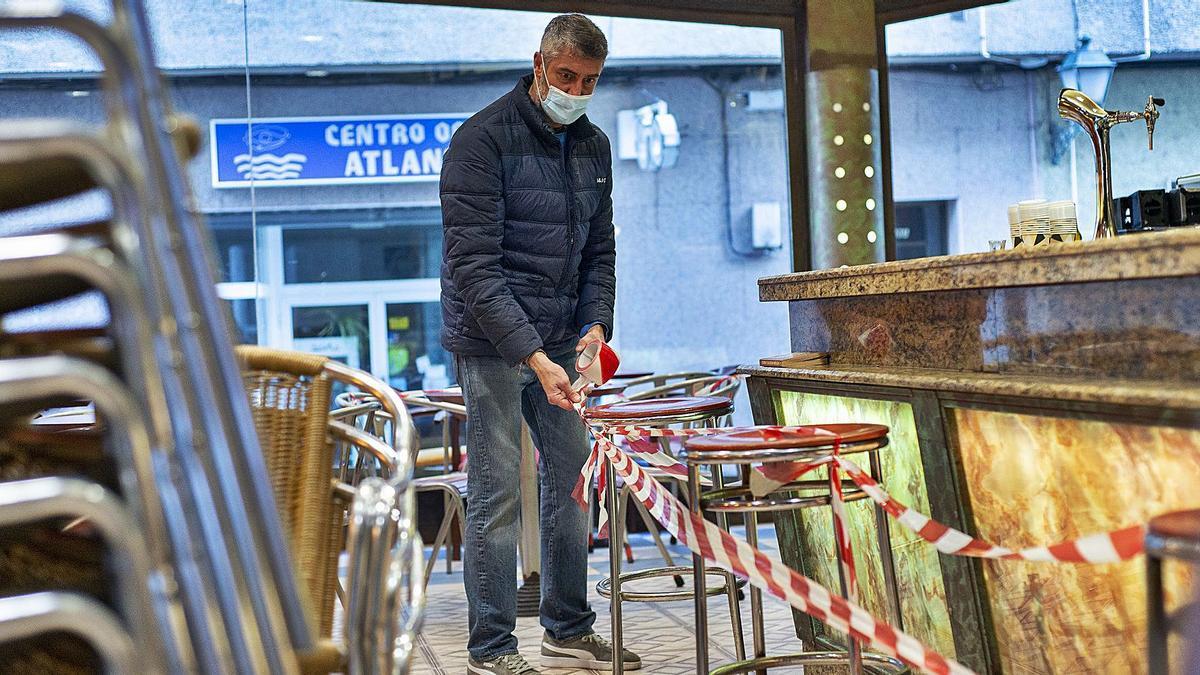 Un hostelero de O Carballiño prepara el interior del local par recibir desde hoy a los clientes.