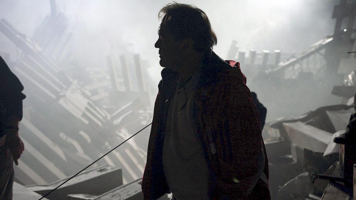 Un hombre camina entre los escombros de las Torres Gemelas.