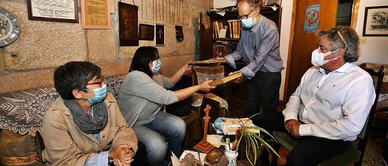 El arcipreste de O Lérez, Vicente Cerdeiriña, muestra libros parroquiales de San Salvador de Poio a las historiadoras