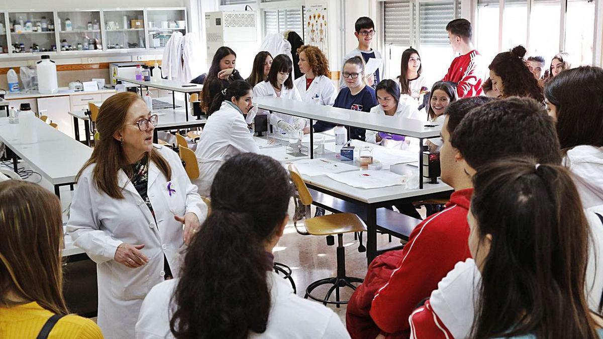 Una profesora explica a los alumnos visitantes el ciclo de FP relacionado con el laboratorio.