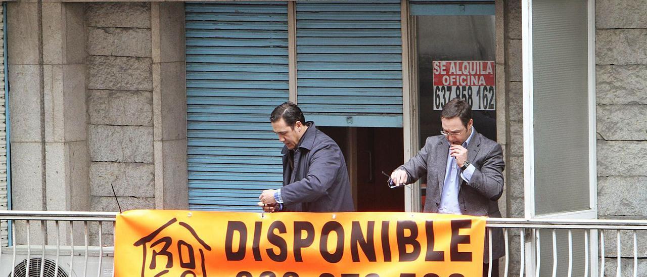 Dos personas cuelgan un cartel  anunciando el alquiler de una  oficina de Ourense.