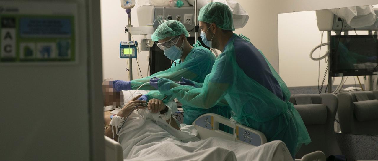 Dos médicos atienden a un hombre en una de las UCI del HUCA.