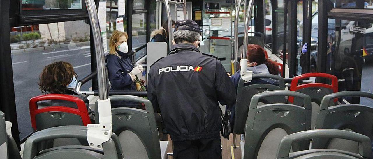 Un agente de la Policía Nacional en un autobús urbano de Vigo. // Alba Villar