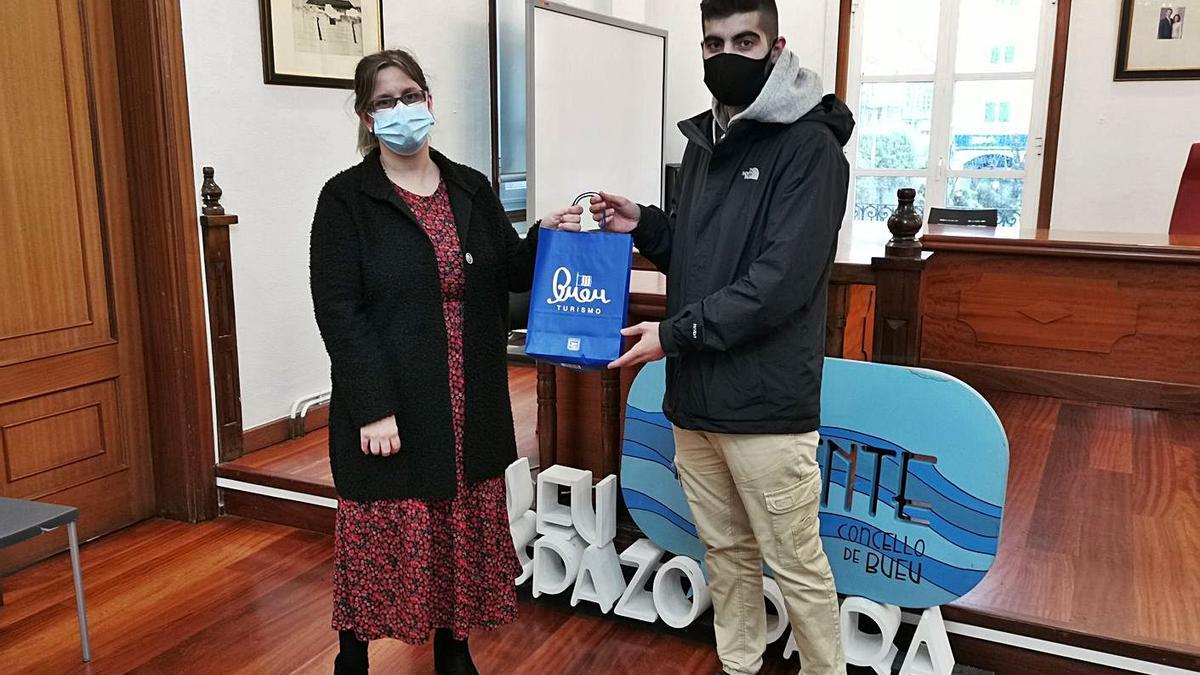 Alberto Moital entrega el lote de libros a la ganadora del concurso.     // SANTOS ÁLVAREZ