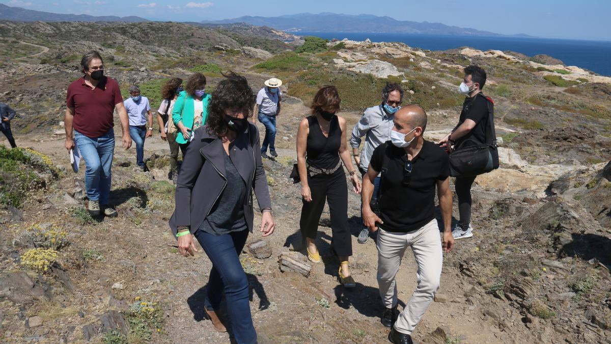 Pla mitjà de la consellera d'Acció Climàtica, Alimentació i Agenda Rural, Teresa Jordà, passejant amb el director del Parc Natural del Cap de Creus Ponç Feliu