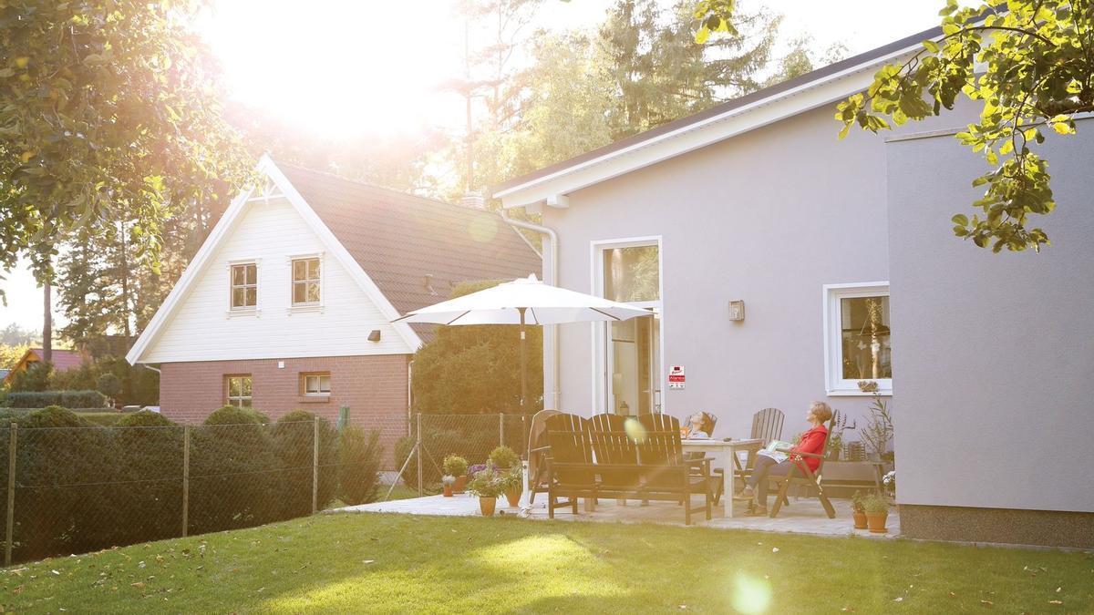 Dos mujeres observan el atardecer en el jardin de una casa.