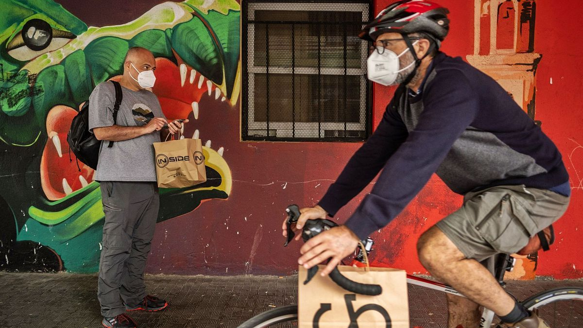 Un ciclista pasea en presencia de un peatón por una calle de La Laguna.