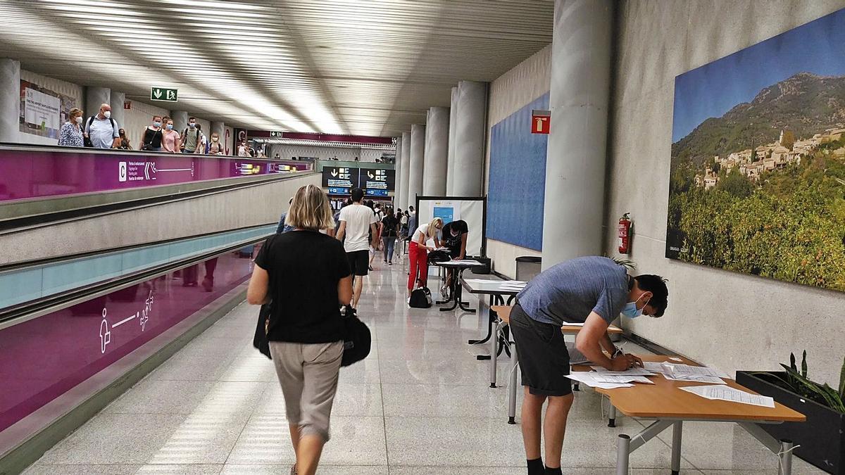 Pasajeros en Son Sant Joan rellenando el documento del control sanitario para viajeros internacionales.