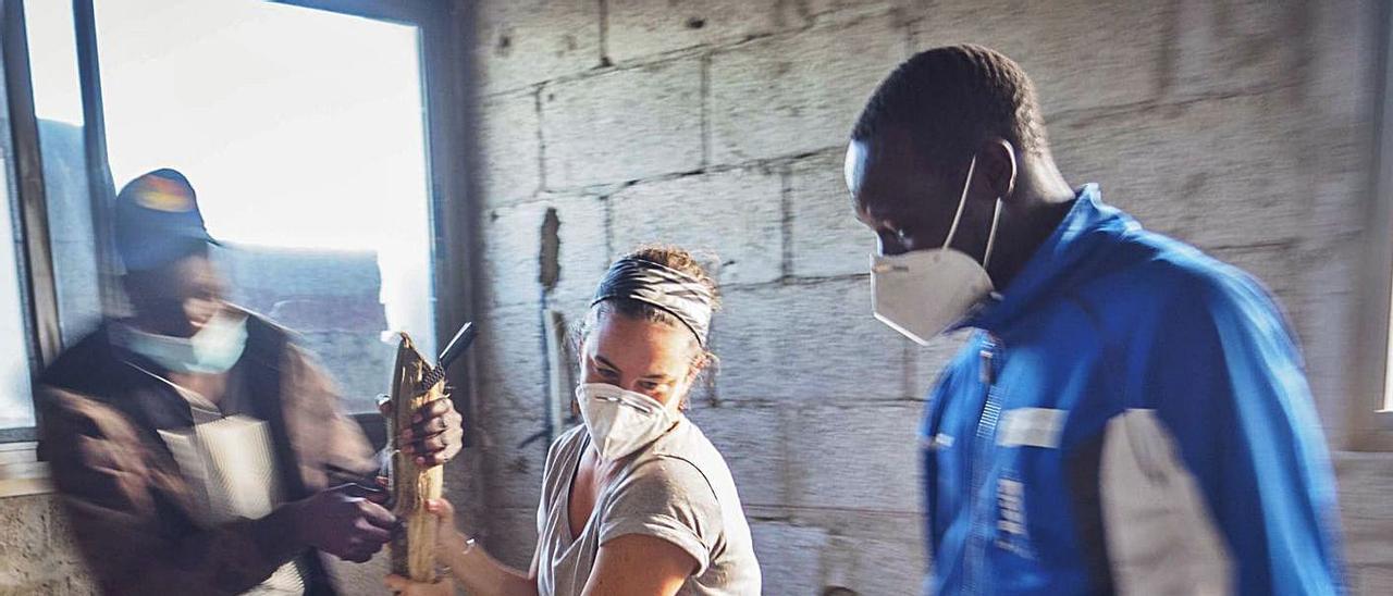 Miriam Suárez, con dos de los jóvenes senegaleses a los que da apoyo de día, organizando las donaciones.     TXEFE BETANCORT