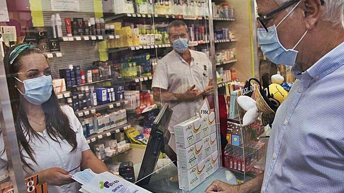 Una professional de la farmàcia Buxó de Manresa dispensant mascaretes quirúrgiques    ARXIU/OSCAR BAYONA