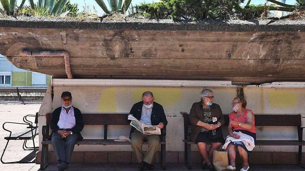 Un grupo de vecinos de Monte Alto descansa en los bancos del barrio.
