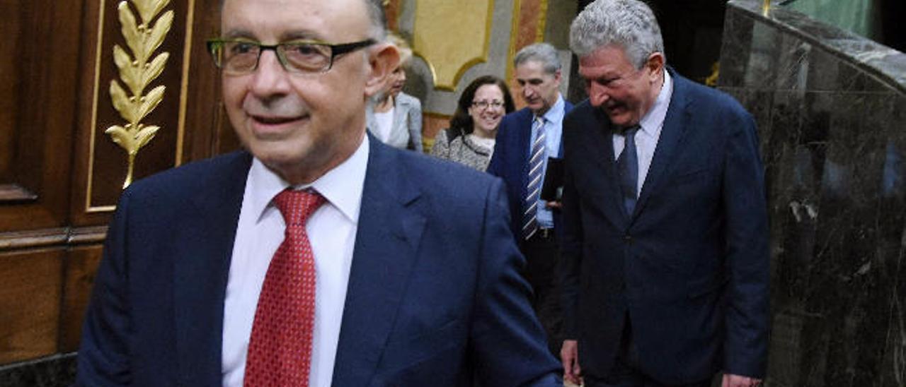 Imagen de archivo del ministro de Hacienda, Cristóbal Montoro, y detrás el diputado de NC en el Congreso de los Diputados.