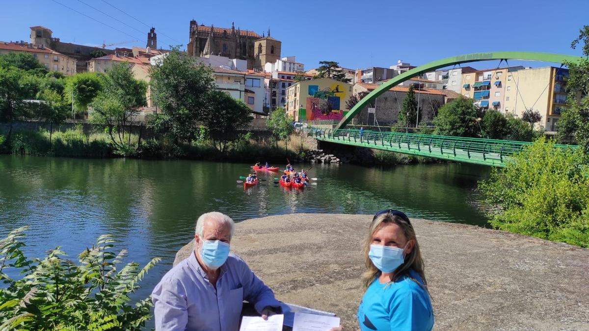 Paco Valverde y Lidia Regidor, con el convenio y los piragüistas al fondo.