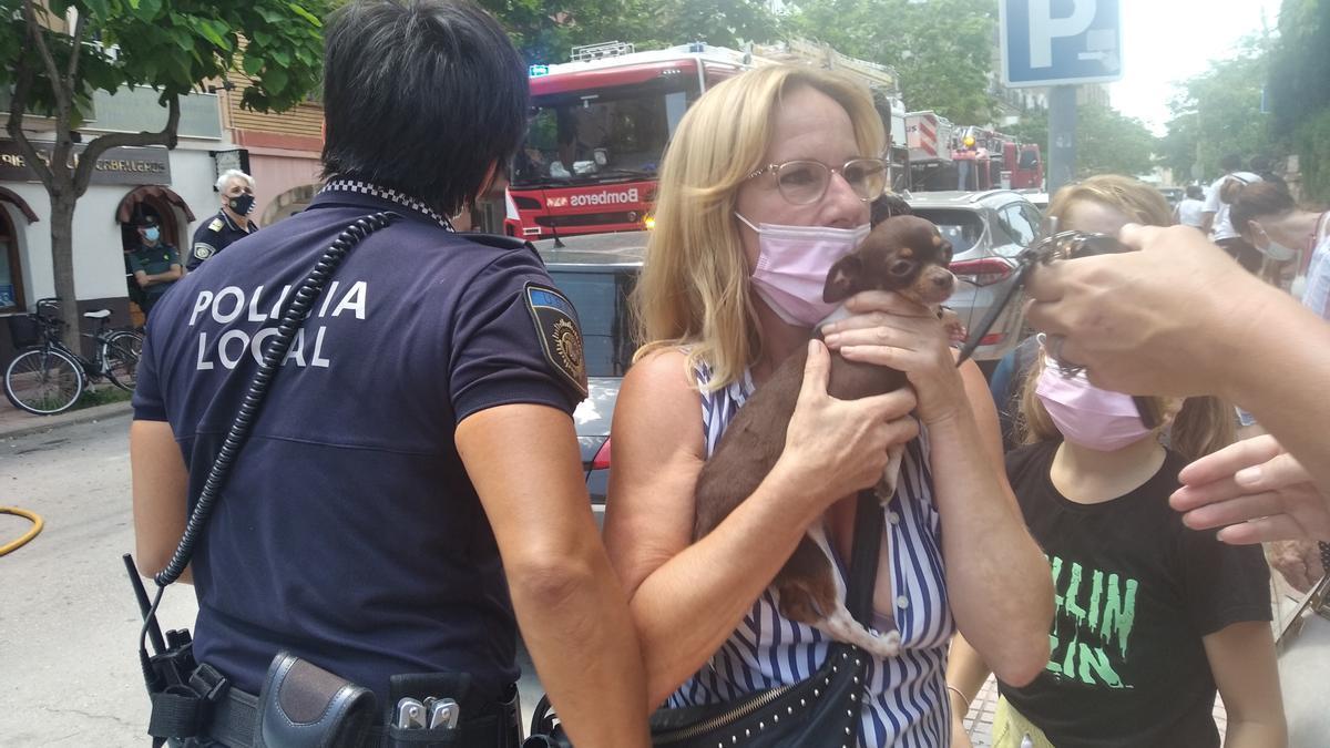 Una agente de la Policía Local entrega a una familia un perrito que se había quedado en un piso