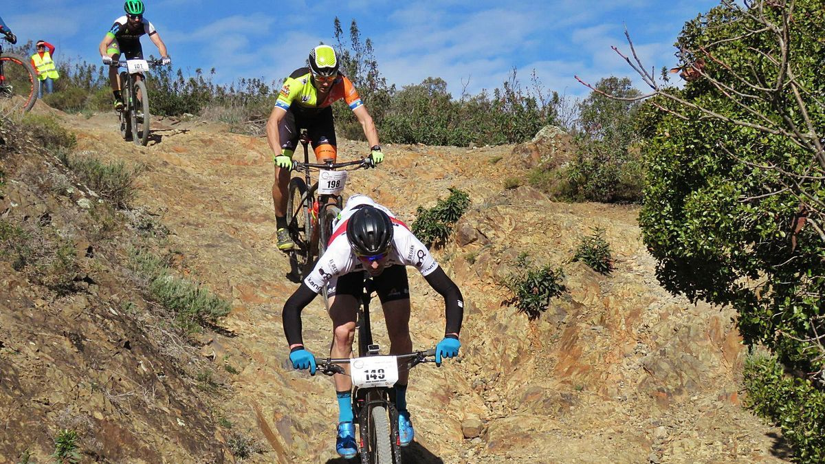 Tres ciclistas durante una prueba deportiva en el medio natural.