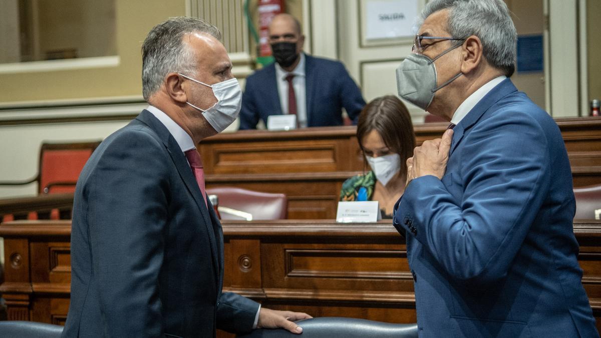Torres conversa con el consejero de Hacienda, Román Rodríguez, este martes en el plano del Parlamento de Canarias.