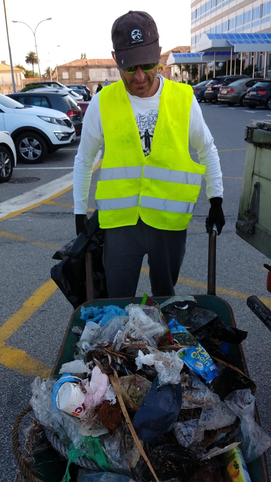 Un voluntario con una carreta repleta de residuos.