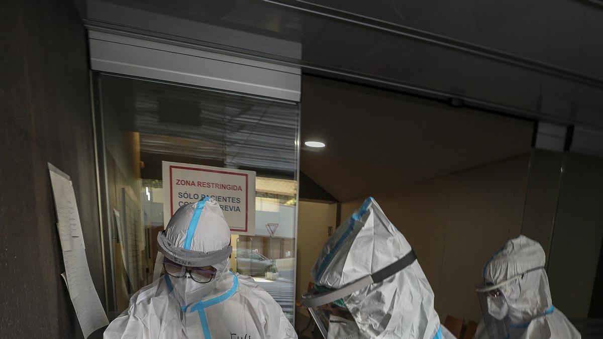 Personal sanitario protegido con EPI se prepara para tomar muestras a pacientes.
