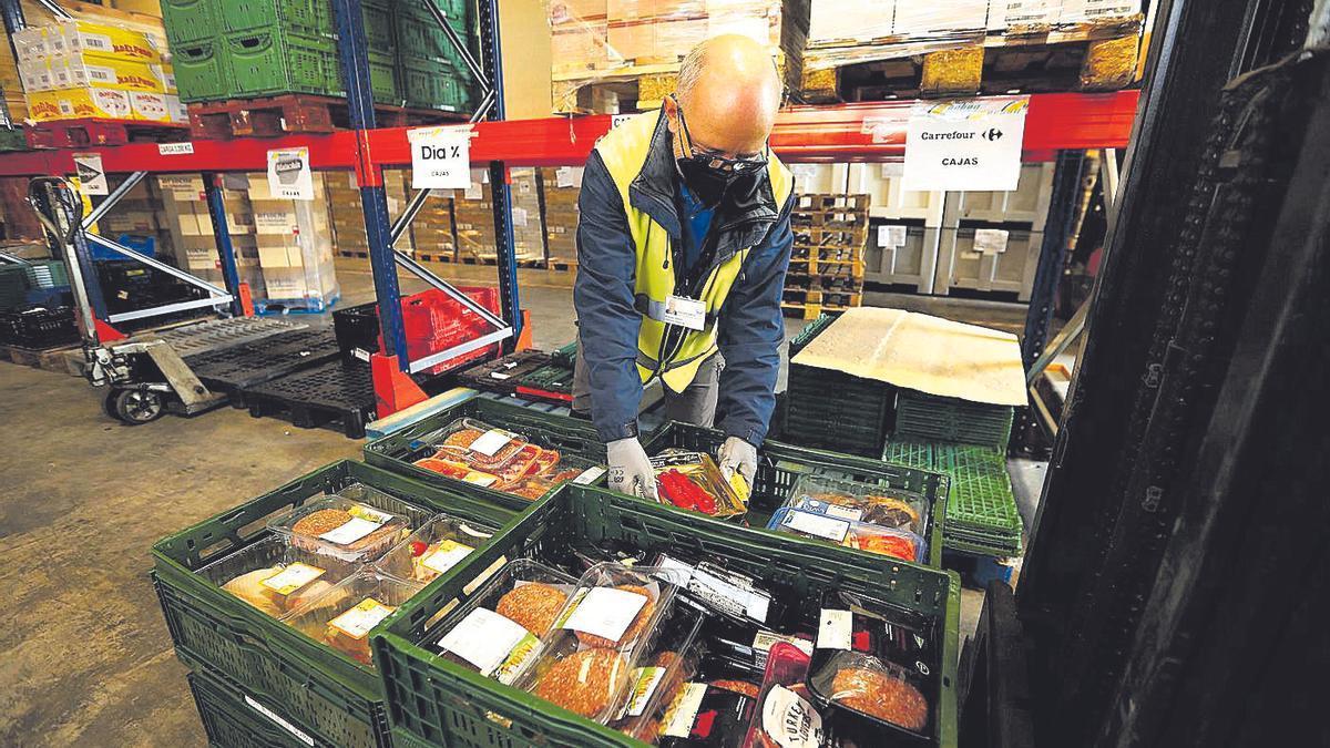 Un hombre apila varias donaciones en una de las últimas recogidas del Banco de Alimentos.