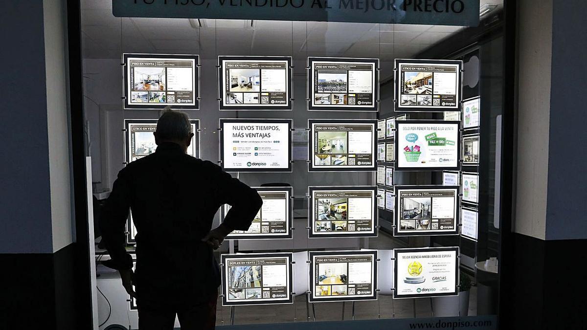 Un hombre mira la oferta de una inmobiliaria de València. | M. A, MONTESINOS